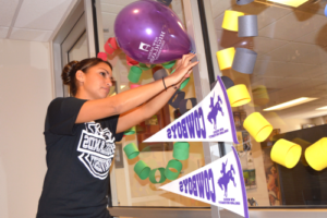 Student decorates with flags and balloons.