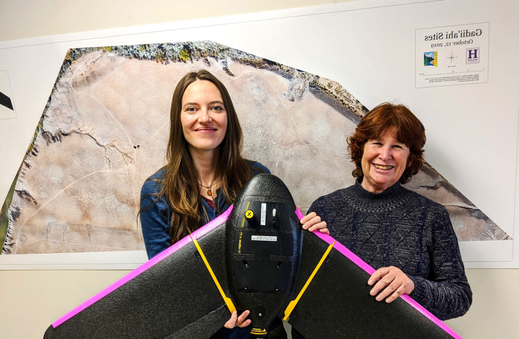 Photo of two instructors holding a large drone.