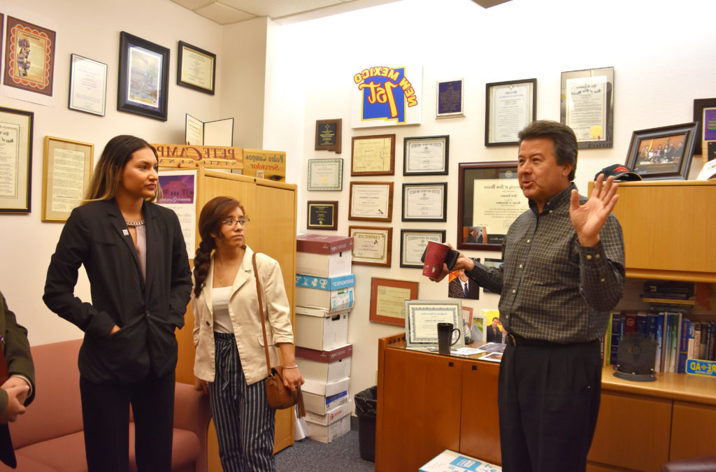 Photo of Senator Campos speaking with two students.